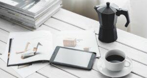 Pracovní stůl s kávou , čtečkou a časopisem